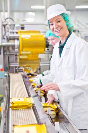 woman handle success: Portrait smiling worker on production line in cheese processing plant