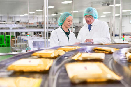 Quality control workers with digital tablet at production line in cheese processing plant