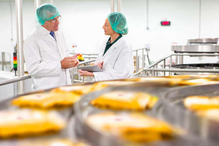 Quality control workers talking behind production line in cheese processing plant Stock Photo