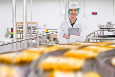 food hygiene: Portrait confident quality control worker at production line in cheese processing plant