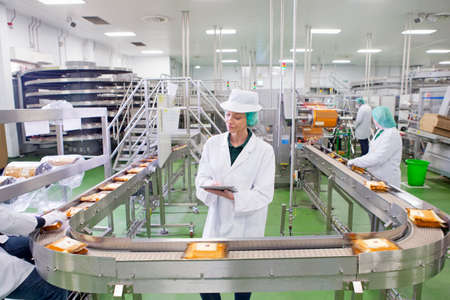 Quality control worker with digital tablet at production line in cheese processing plant