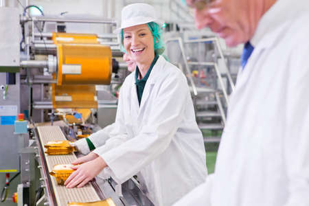 woman handle success: Portrait smiling worker stacking cheese on production line in processing plant