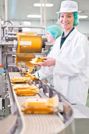 woman handle success: Portrait smiling worker with cheese at production line in processing plant