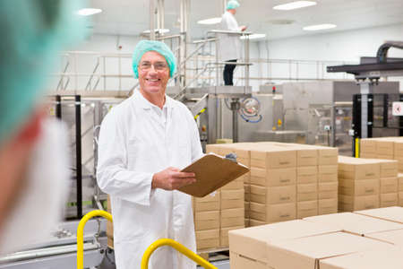 Portrait smiling worker with clipboard at food packaging production line