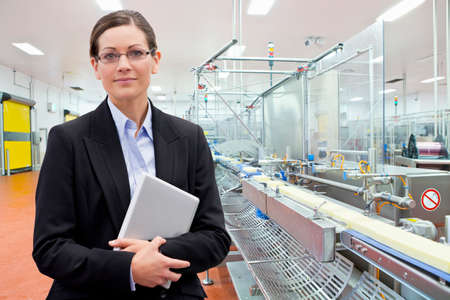 Portrait confident businesswoman with laptop at production line in cheese processing plant