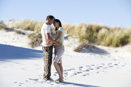 adult footprint: A young couple walking in sand dunes LANG_EVOIMAGES