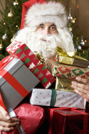 Father ChristmasSanta Claus holding a pile of presents Stock Photo