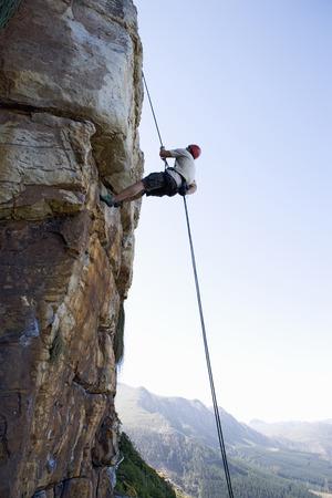 scaling: A climber climbing a rock face