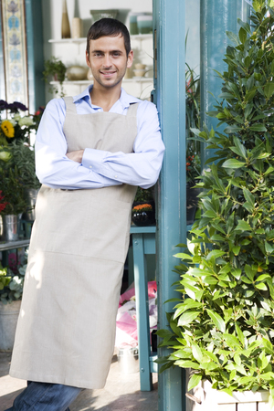 fulfilled: Male florist standing at the entrance to his shop