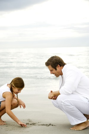 crouches: A father and daughter on a beach LANG_EVOIMAGES