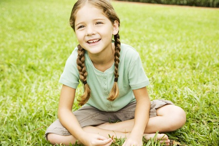 little girl with pigtails sitting cross legged on the grass Stock Photo