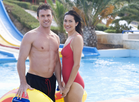 A couple standing by a pool in a waterpark