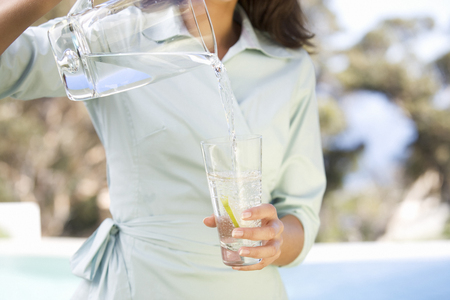 replenish: Woman pouring a glass of water
