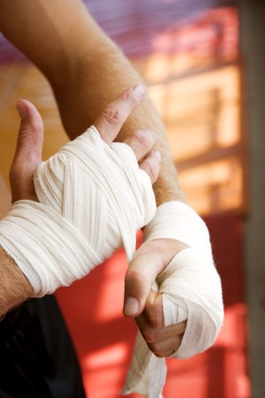 Boxer binding up hands with padding bandages Stock Photo