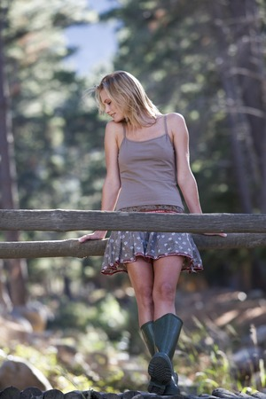 A young woman standing on a wooden bridge in a forest