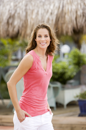 Portrait of woman outdoors at a tropical holiday resort, walking along Stock Photo