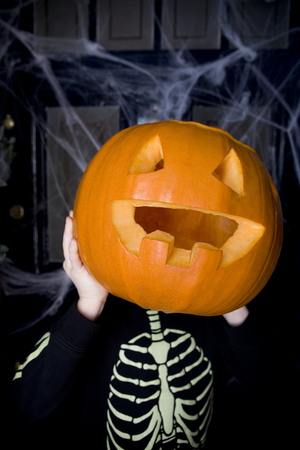 skeleton costume: Child in a skeleton costume at a Halloween party, holding a pumpkin with a carved face