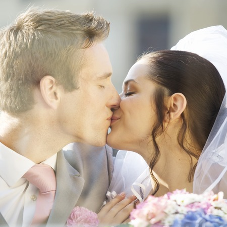 together with long tie: A bride and groom kissing LANG_EVOIMAGES