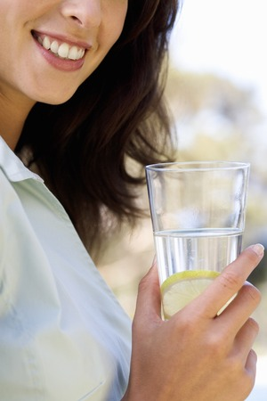 well beings: Woman holding a glass of water, close-up