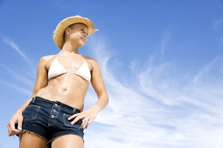 A young woman in bikini, shorts and hat