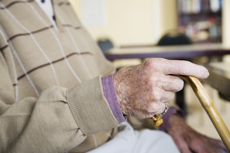 An elderly man holding a walking stick
