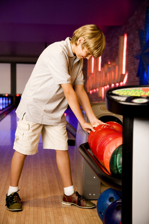 Boy in a bowling alley choosing a bowling ball
