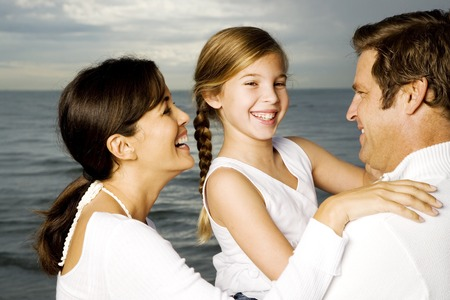 carries: A couple with their daughter on a beach