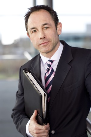 Portrait of a businessman holding a leather case with briefing papers