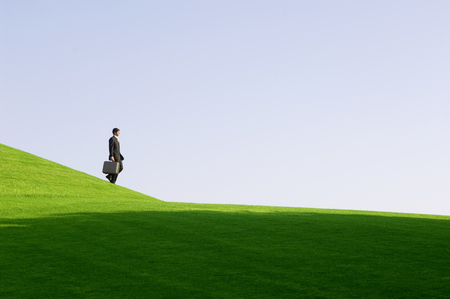 almost all: A businessman with a suitcase walking down hill