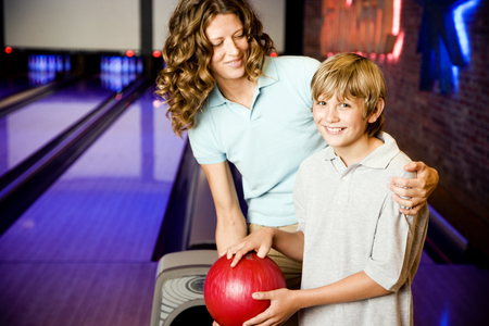 Mother and son in a bowling alley, holding red bowling ball LANG_EVOIMAGES