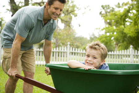 father giving son ride in the wheelbarrow