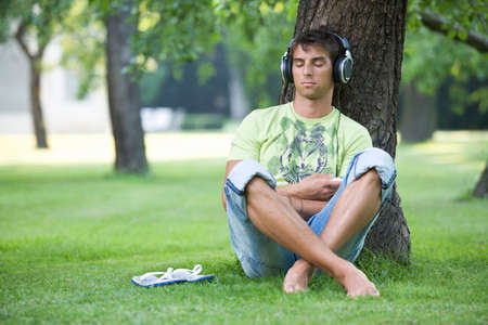 A teenage boy sitting in a park listening to music