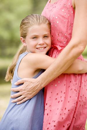 girl hugging woman around the waist LANG_EVOIMAGES