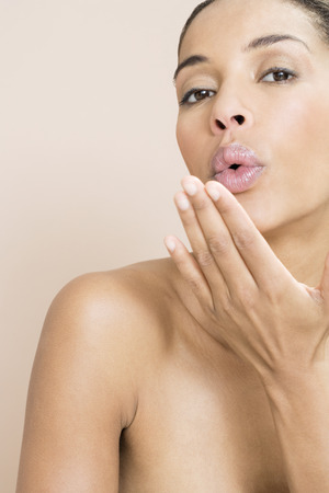 puckered lips: A woman blowing a kiss