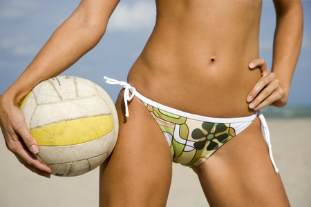 tummy time: A young woman on a beach holding a ball