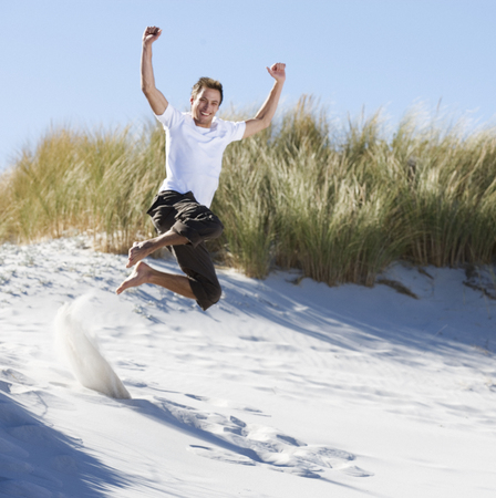 Young man jumping in sand dunes