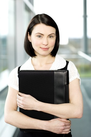 Young businesswoman standing on office walkway holding folder of papers Stock Photo
