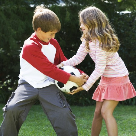 sibling rivalry: Young boy and girl playing with a football in a garden