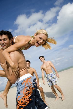 teases: A young woman in a bikini with three male admirers
