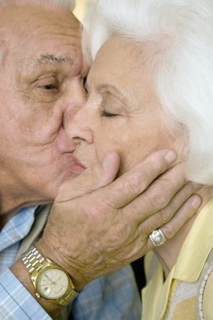 80 plus years: An elderly couple kissing LANG_EVOIMAGES