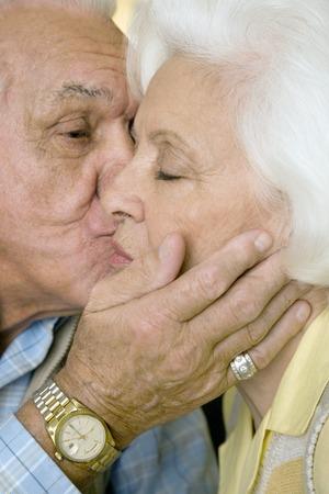 retiring: An elderly couple kissing LANG_EVOIMAGES