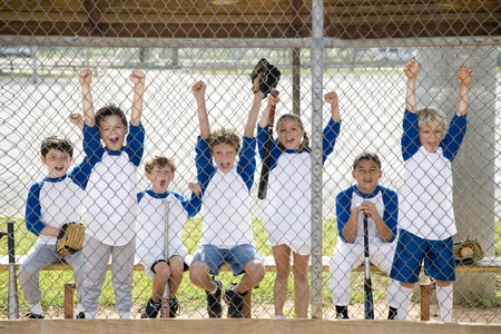 little league: Little league baseball team cheering behind wire fence LANG_EVOIMAGES