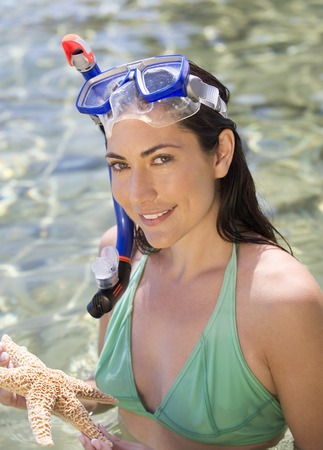 A female snorkeler holding a starfish