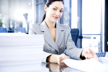 Smiling woman behind a desk full of paperwork Stock Photo
