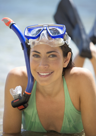 A woman wearing snorkeling equipment lying on a beach Stock Photo