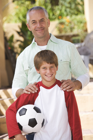 Portrait of a father with his young son, holding a football