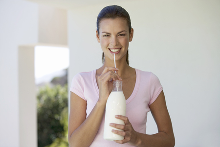 A woman drinking milk through a straw LANG_EVOIMAGES