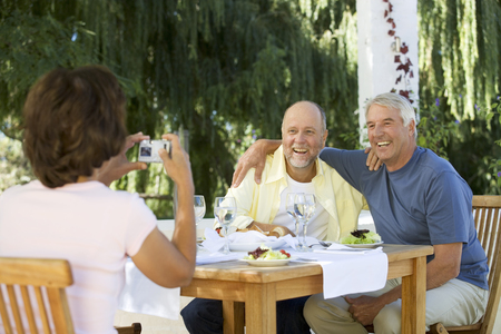 A group of senior couples at a restaurant, woman taking picture with digital camera