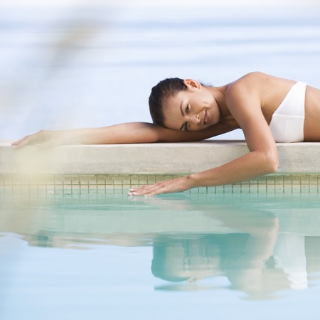 A young woman laying by a pool Banco de Imagens