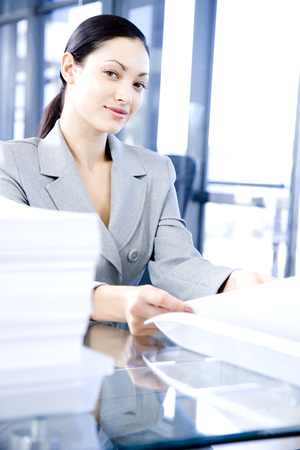 Businesswoman behind a desk with paperwork Stock Photo